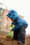 Мальчик играет в ящике с песком с лопаткоулавливателем детей на спортивной площадке Стоковые Изображения