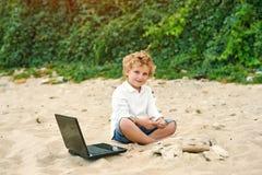 Мальчик играет на пляже, лежа рядом с компьтер-книжкой Стоковая Фотография RF