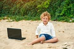 Мальчик играет на пляже, лежа рядом с компьтер-книжкой Стоковые Изображения RF