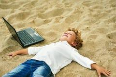 Мальчик играет на пляже, лежа рядом с компьтер-книжкой Стоковые Фотографии RF