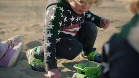 Мальчик играет с самосвалом зеленого цвета игрушки на пляже видеоматериал