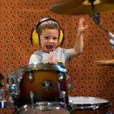 Мальчик играя барабанчики с наушниками защиты стоковое фото