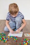 Мальчик играя в мозаике стоковая фотография