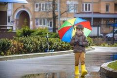 Мальчик играя в ненастном парке лета Ребенок при красочный зонтик радуги, водоустойчивое пальто и ботинки скача в лужицу и грязь Стоковое фото RF
