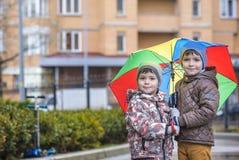 Мальчик играя в ненастном парке лета Ребенок при красочный зонтик радуги, водоустойчивое пальто и ботинки скача в лужицу и грязь Стоковые Фотографии RF
