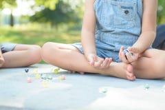 Мальчик играя игру мраморов снаружи Стоковое Фото