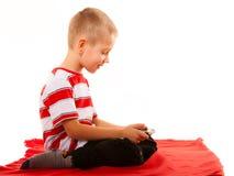 Мальчик играя игры на smartphone Стоковые Фото