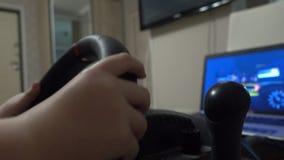 Мальчик играя компютерную игру гонок используя рулевое колесо видеоматериал