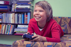 Мальчик играя консоль видеоигры Стоковое фото RF