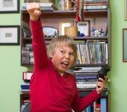 Мальчик играя консоль видеоигры Стоковая Фотография RF
