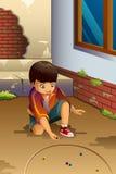 Мальчик играя мраморы Стоковые Изображения