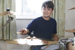 Мальчик играя набор барабанчика дома Стоковые Фото
