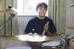 Мальчик играя набор барабанчика дома Стоковое Изображение