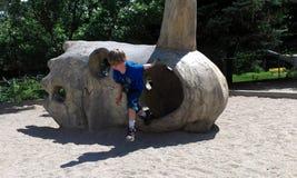 Мальчик играя на парке dino Стоковые Изображения