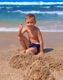 Мальчик играя на пляже стоковое изображение rf