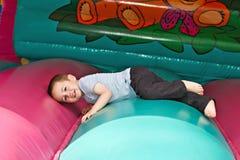 Мальчик играя на раздувном скольжении Стоковое фото RF