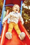Мальчик играя на скольжениях детей Стоковая Фотография