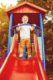 Мальчик играя на скольжениях детей Стоковые Фото