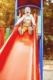 Мальчик играя на скольжениях детей Стоковое Изображение