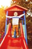 Мальчик играя на скольжениях детей Стоковые Фотографии RF