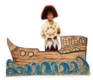 Мальчик играя пирата отсутствие управления рулем корабля картона Стоковое Изображение
