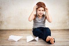 Мальчик играя с бумажными самолетами Стоковые Изображения