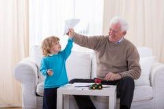 Мальчик играя с бумажным самолетом Стоковая Фотография RF