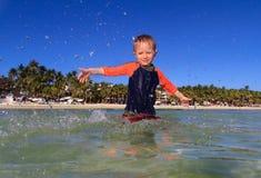 Мальчик играя с водой на пляже Стоковые Фотографии RF