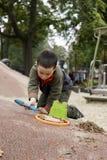 Мальчик играя с лопаткоулавливателем и ведром стоковая фотография rf