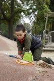 Мальчик играя с лопаткоулавливателем и ведром стоковые фото