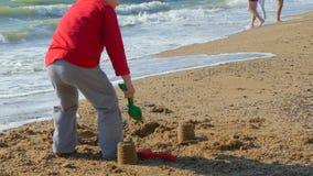 Мальчик играя с песком на пляже морем видеоматериал