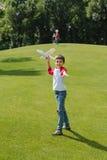 Мальчик играя с самолетом игрушки на зеленом луге в парке Стоковое фото RF
