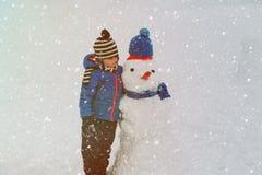 Мальчик играя с снеговиком в природе Стоковое фото RF