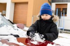 Мальчик играя с снегом снаружи Стоковая Фотография
