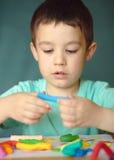 Мальчик играя с тестом игры цвета Стоковая Фотография RF