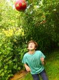 Мальчик играя с дуновением головы футбола тренировки шарика Стоковые Фото