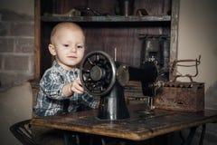 Мальчик играя с шить-машиной Стоковые Изображения RF