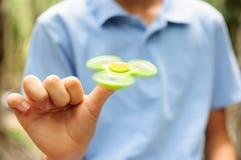 Мальчик играя с Tri обтекателем втулки руки непоседы Стоковые Изображения