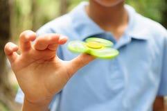 Мальчик играя с Tri обтекателем втулки руки непоседы Стоковая Фотография RF