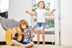 Мальчик играя танцы гитары и девушки Стоковые Фотографии RF
