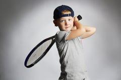 Мальчик играя теннис Дети спорта Ребенок с ракеткой тенниса стоковое фото rf