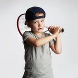 Мальчик играя теннис Дети спорта Ребенок с ракеткой тенниса стоковые изображения rf