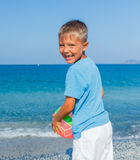 Мальчик играя шарик на пляже стоковое изображение