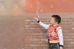 Мальчик играя soapbubbles Стоковые Фотографии RF