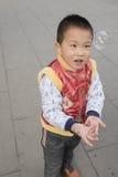 Мальчик играя soapbubbles Стоковое Фото