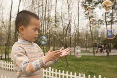Мальчик играя soapbubbles Стоковые Фото