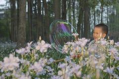 Мальчик играя soapbubbles Стоковая Фотография RF
