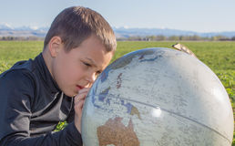 Мальчик изучая глобус Стоковая Фотография