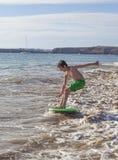 Мальчик имеет потеху бежать с surfboard в волнах стоковые изображения rf