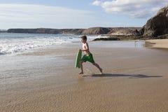 Мальчик имеет потеху бежать с surfboard в волнах стоковое фото